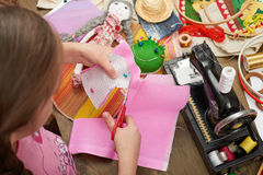 Girl sews doll clothes, top view, sewing accessories top view, seamstress workplace, many object for needlework, handmade and hand Royalty Free Stock Photos