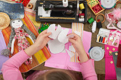 Girl sews doll clothes, top view, sewing accessories top view, seamstress workplace, many object for needlework, handmade and hand Royalty Free Stock Photography