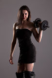 Girl in sexy black dress lifting weights Stock Images