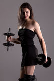 Girl in sexy black dress lifting weights Royalty Free Stock Photography