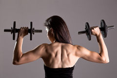Girl in sexy black dress lifting weights Stock Photos