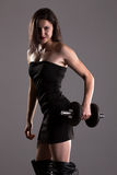 Girl in sexy black dress lifting weights Stock Image