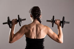 Girl in sexy black dress lifting weights Royalty Free Stock Image