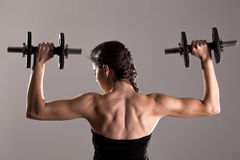 Girl in sexy black dress lifting weights Stock Photo