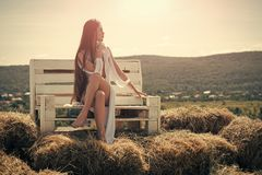 Girl in sexy dress sit on wooden bench. Woman with long hair on sunny day on mountain landscape. Beauty, look concept. Fashion, summer style. Vacation, travel Royalty Free Stock Photos