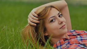 Girl sexy lying on green grass outdoors slow motion stock video footage