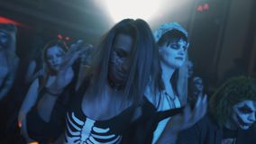 Girl in sexy skeleton suit and face paint dancing in crowd at halloween party stock video footage