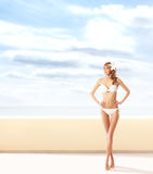 A girl in a sexy swimsuit on a light blue background Royalty Free Stock Photos