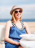 Girl in shades in cafe on the beach Royalty Free Stock Photo