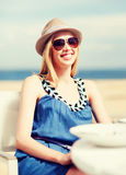 Girl in shades in cafe on the beach Royalty Free Stock Images