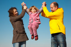 Girl shakes on hands at parents against sky Stock Photo