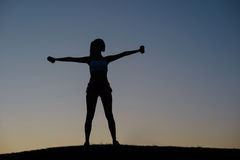 Girl shakes her muscles on the sunset background. Stock Photo