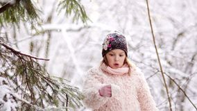 The girl shakes the snow from the tree branch in the forest. Happy childhood. Winter fun.  stock footage