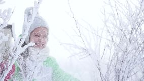 Girl shakes the snow from the tree branch in the forest. Happy childhood. Winter fun. Happy girl shakes the snow from the tree branch in the forest. Happy stock footage