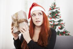 Girl is shaking happy christmas present Royalty Free Stock Image
