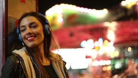 Girl shaking her head to the rhythm of music with headphones stock video footage