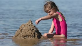 A girl in the shallows of the river sent a large pile of sand stock video
