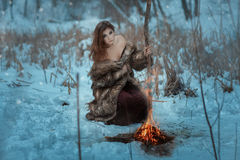 Girl shaman is heated by fire in winter forest. Stock Photography