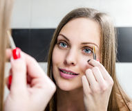 Girl shaping eyebrows with tweezer Royalty Free Stock Image
