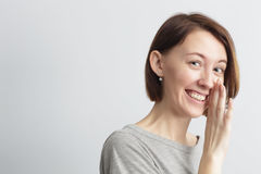 Girl shares with secret whispering, covering mouth with hand Stock Photos