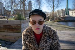 Girl with shaved blond hair and with alternative outfit and sunglasses. Leopard jacket stock photos