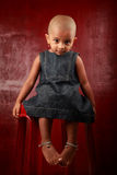 Girl with shaved head. Sits on a chair in a red background Royalty Free Stock Image