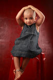 Girl with shaved head. Little girl with shaved head shows a funny gesture in a red background Royalty Free Stock Photography