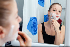 Girl shaving in bathroom Royalty Free Stock Image