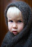 Girl in shawl. Serious little girl in big shawl Stock Photo