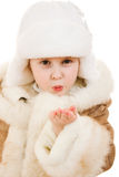Girl in a sheepskin coat and cap sends a kiss Royalty Free Stock Photos