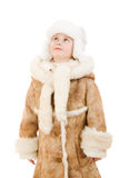 Girl in a sheepskin coat and hat looking up Stock Photo