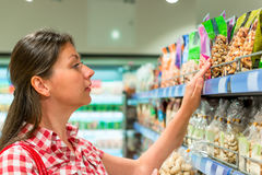 Girl on the shelf  chooses the nuts Stock Photography
