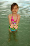 Girl with Shell. Little girl standing in the ocean and holding a small conch shell in her hands royalty free stock image