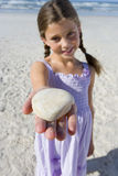 Girl (5-7) with shell on beach, smiling, portrait (differential focus) Royalty Free Stock Image