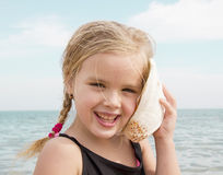 Girl with shell listening to the sea Stock Image