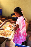 Girl shelling cashew nuts Stock Photos