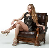 Girl in a shiny dress, sitting on chair Royalty Free Stock Images