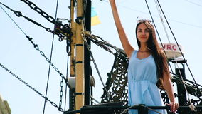 Girl on the ship on the background National colours of Ukraine. Brunette Girl on the ship waving his hand in greeting. Girl brunette in a blue dress on a ship stock video