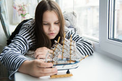 Girl with a ship on the window sill dreaming of voyages Royalty Free Stock Photo