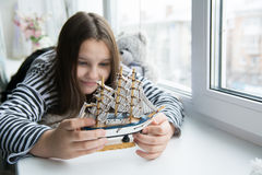 Girl with a ship on the window sill dreaming of voyages Royalty Free Stock Photography