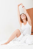Girl in shirt awaking on white sheet in bed at home Stock Photography