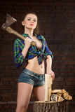 Girl in shirt chopping wood with an ax Royalty Free Stock Photos