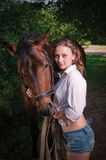 Girl in a shirt and a horse Royalty Free Stock Photos