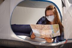 A girl in shirt, jeans, sunglasses and medical masks sits in tent and looks at map. Open borders, choice of route. Travel at home