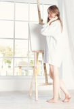Girl in a shirt near large window. morning with his easel Royalty Free Stock Photo