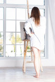 Girl in a shirt near large window. morning with his easel Royalty Free Stock Images