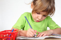 Girl in shirt painting in notebook Royalty Free Stock Images