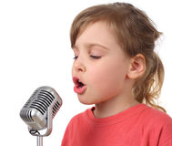 Girl in shirt singing in microphone, half body Stock Image