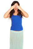 Girl in a shirt and skirt covering her eyes isolated Stock Images