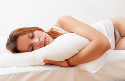 Girl in shirt sleeping on white pillow in bed at home Stock Images